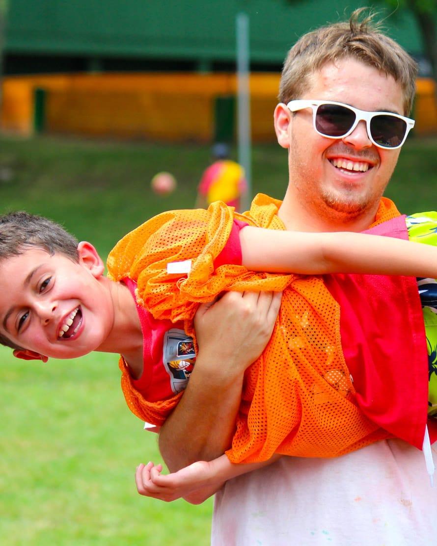 Staff wearing sunglasses holding camper in scrimmage vest