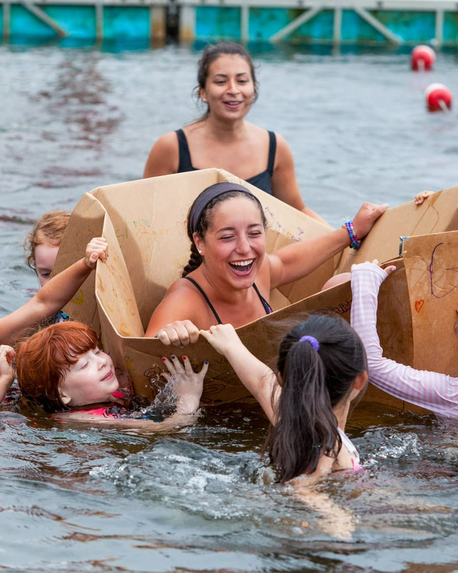 Camp staff in cardboard box in lake during special event